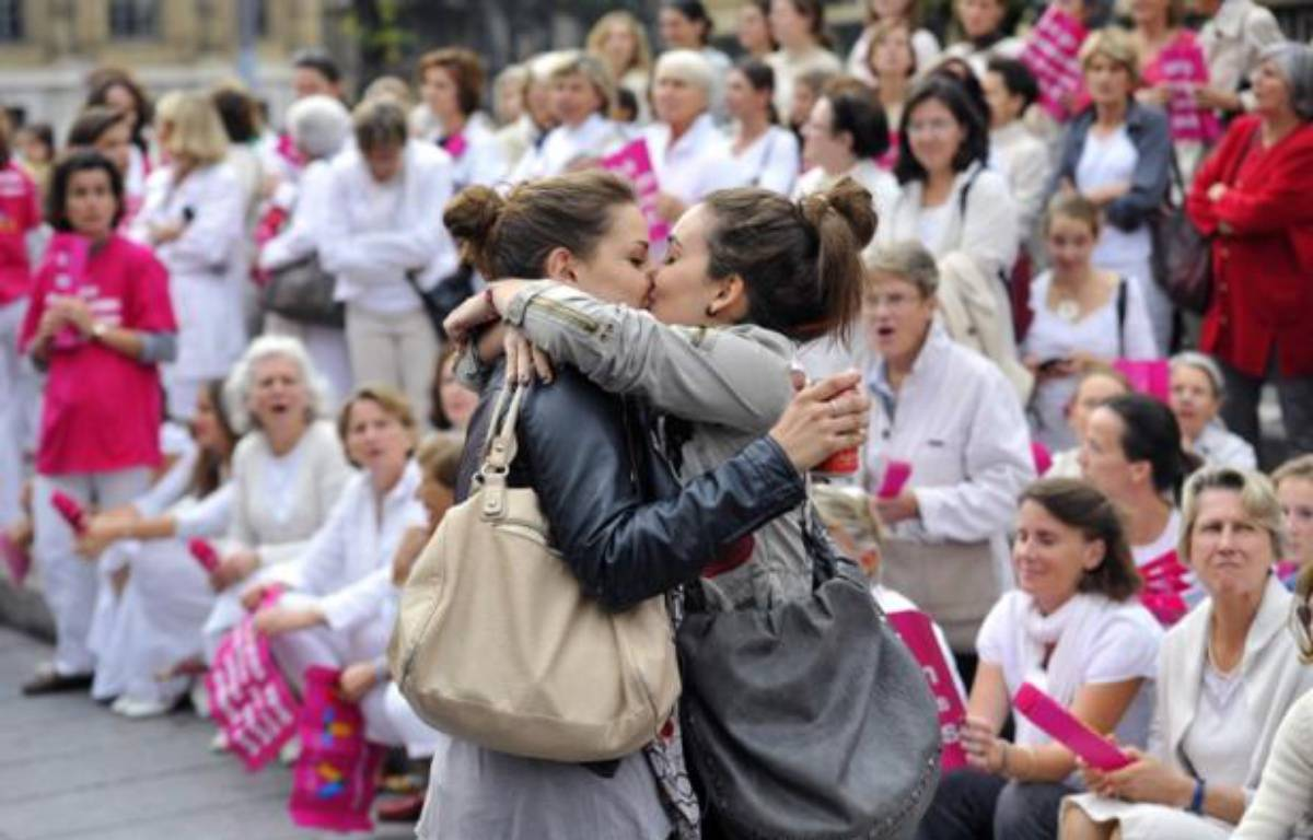 Deux jeunes filles s'embrassent à Marseille, le 23 octobre 2012, lors d'une manifestation anti-mariage pour tous organisée par l'association Alliance Vita. – AFP/ Gérard Julien