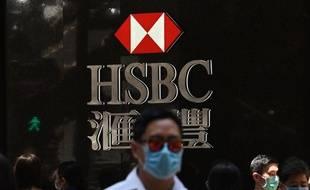 Un homme masqué devant le logo de la banque HSBC.
