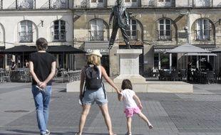 Des touristes devant la statue « Eloge du pas de côté » place du Bouffay à Nantes.