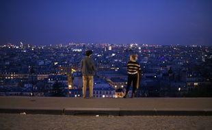 Ambiance dans le quartier de Montmartre. Un couple se tenant a distance en haut des marches aboutissant au Sacre-Coeur, le 18 mars 2020.
