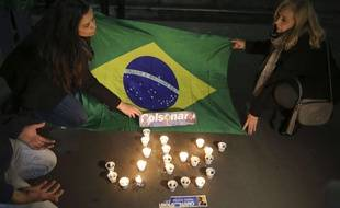 Des supporteurs du candidat brésilien d'extrême droite Jair Bolsonaro, gravement blessé au couteau, allument des bougies le 6 septembre 2018.