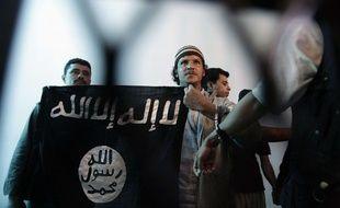 Un militant d'Al-Qaida au Yémen brandit le drapeau islamiste, frappé de la chahada, lors d'une audience à Sanaa, le 23 avril 2013.