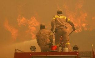 Des pompiers tentent d'éteindre l'incendie au Nord-Est d'Athènes, le 22 août 2009