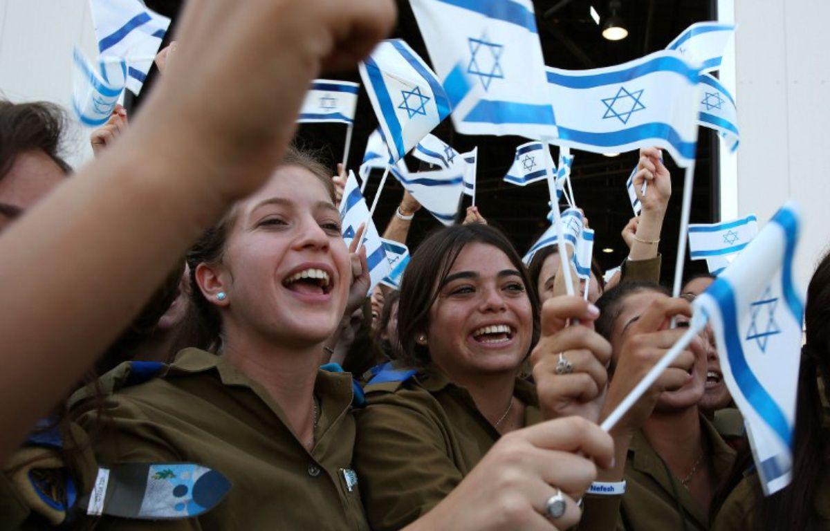 De jeunes femmes qui ont fait leur aliyah brandissant un drapeau israélien. – GALI TIBBON
