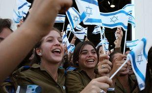 De jeunes femmes qui ont fait leur aliyah brandissant un drapeau israélien.