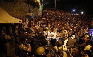 Des forces de sécurité israéliennes se tiennent devant des fidèles musulmans palestiniens qui prient le 23 juillet 2017 à l'extérieur de la porte des Lions, entrée principale de la mosquée Al-Aqsa à Jérusalem, afin de protester face aux nouvelles mesures de sécurité imposées par Israël.