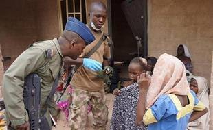 Photo fournie par l'armée nigériane le 30 avril 2015 prise dans un lieu non divulgué de l'Etat de Borno montrant un militaire discutant avec des jeunes filles libérées lors d'une opération contre le groupe islamiste Boko Haram