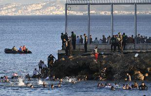 Des officiers de la Guardia Civil espagnole tentent d'empêcher les Marocains de nager et d'entrer sur le territoire espagnol à la frontière du Maroc et de l'Espagne, dans l'enclave espagnole de Ceuta, le lundi 17 mai 2021.