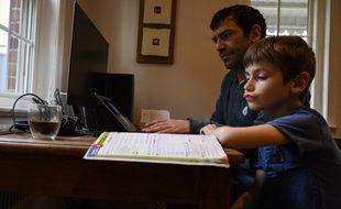Un enfant qui suit l'école à la maison en mars 2020.