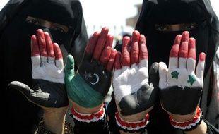 Des manifestants montrent leurs mains aux couleurs de la Libye pré-Kadhafi, la Syrie et le Yémen, vendredi 21 octobre, lors d'une manifestation à Sanaa, au Yémen.