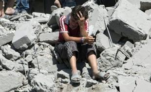 Un jeune garçon est effondré le 21 juillet 2015 sur les décombres de maisons dans un vieux quartier d'Alep, au nord de la Syrie, bombardé par l'aviation syrienne