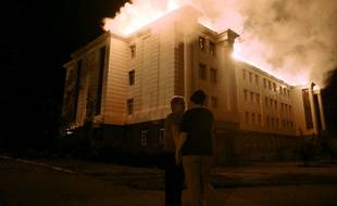 Bystanders watch a fire consuming a school in downtown Donetsk on August 27, 2014, after being hit by a shelling. Several civilians died when their car was completely burned after being hit by shell fragments in central Donetsk, the rebel-held city in eastern Ukraine.  AFP PHOTO/ FRANCISCO LEONG