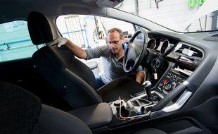 Un technicien d'un centre automobile inspecte un véhicule.