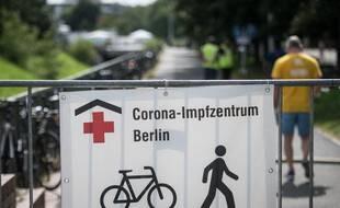 Une banderole montre le chemin vers un centre de vaccination à Berlin alors que les gens arrivent pour se faire vacciner contre le coronavirus, le 30 juillet 2021.