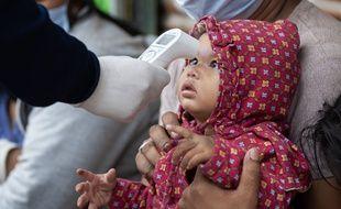 Un soignant népalais prend la température d'un enfant à Katmandou, le 27 avril 2020 (illustration).