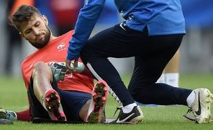 France's goalkeeper Benoit Costil (L) grimaces after injury during a training session, on September 5, 2015 at the stadium in Bordeaux, two days before the Euro 2016 friendly football match between France and Serbia on September 7.  AFP PHOTO / FRANCK FIFE