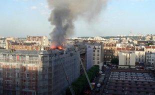 Des pompiers sur une échelle pour tenter d'éteindre l'incendie qui s'est déclaré dans un immeuble résidentiel d'Aubervilliers, en banlieue parisienne, le 7 juin 2014