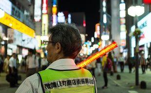 Un membre de la patrouille chargée d'informer les clients des risques d'escroquerie dans le quartier de Kabukicho à Tokyo, le 24 juin 2015.