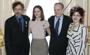 L'actrice Marion Cotillard et le réalisateur américain Tim Burton posent aux côtés de Frédéric Mitterrand, ministre de la Culture, après avoir été décorés Chavaliers des Arts et des Lettres au Ministère de la Culture, le 15 mars 2010. Tim Burton est accompagné de son épouse, l'actrice Helena Bonham Carter.