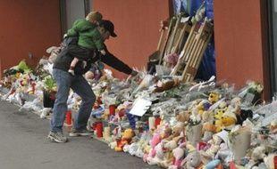 """A l'église ou devant la crèche """"Le Pays des Fables"""", les habitants de Termonde, dans l'ouest de la Belgique, rendaient dimanche hommage aux deux bébés et à la puéricultrice tués vendredi par un forcené."""