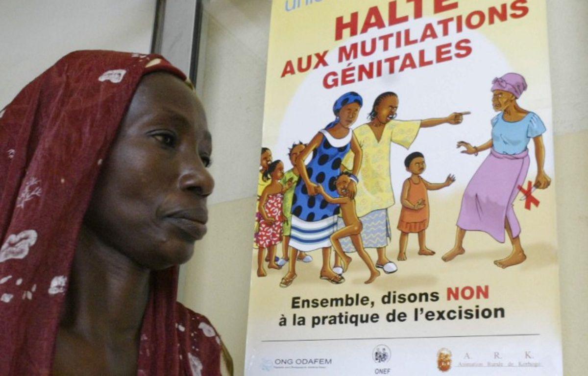 Une femme devant une affiche anti-excision à Abidjan, en 2005. – KAMBOU SIA / AFP