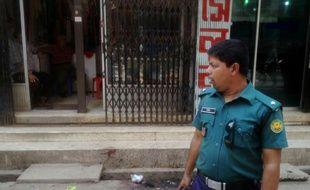 Un policier bangalais surveille l'entrée du lieu du meurtre d'un étudiant en droit, défenseur de la laïcité, à Dacca la 7 avril 2016