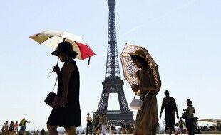Des touristes se protègent du soleil à Paris.