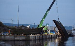 Des bateaux nords coréens qui se sont échoués sur les côtes japonaises, sont sortis de l'eau par une grue, le 21 novembre 2015.