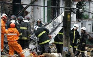 Les secours s'activent autour de l'épave de l'avion qui s'est écrasé dimanche sur une maison, dans le quartier de Sao Paulo