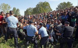 Hommes, femmes et enfants tentent de rompre un cordon de policiers le 17 septembre 2015 dans la ville de Tovarnik, près de la frontière serbo-croate