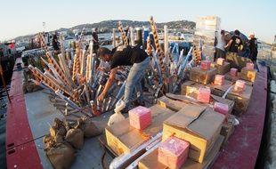 Des artificiers polonais installent les bombes qui composeront leur feu d'artifice sur une barge au Vieux port de Cannes, le 12 juillet 2018