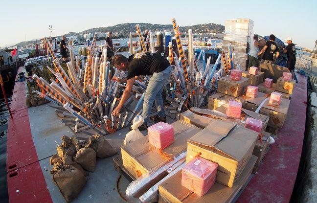 Des artificiers installent les bombes de leur feu d'artifice sur une barge au Vieux port de Cannes, le 12 juillet 2018