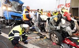 Les secours s'affairent le 31 octobre 2009 autour d'un véhicule accidenté sur l'autoroute A54 entre Arles et Nîmes.