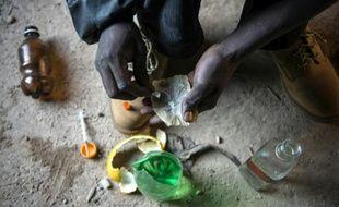 Un toxicomane prépare son injection, dans un bâtiment abandonné de la périphérie de Johannesbourg, en Afrique du Sud, le 17 juillet 2015