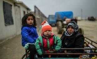 Des enfants et une femme syriens arrivent à Bab al-Salama d'où ils espèrent pouvoir entrer en Turquie dont la frontière est toujours fermée, le 6 février 2016