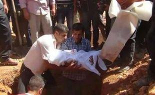 Le père du petit Aylan Kurdi (c) tient entre ses bras la dépouille de son fils avant son enterrement à Kobané en Syrie, le 4 septembre 2015