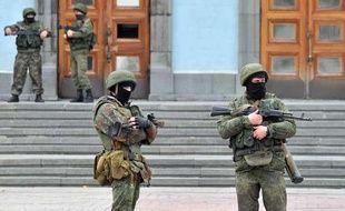 Des hommes non-identifiés en uniforme et armés gardent l'entrée du bâtiment abritant le gouvernement de Crimée, à Simferopol le 2 mars 2014.