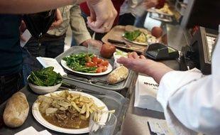 """Une personne procède  au paiment de son déjeuner au sein du restaurant collectif du CNRS à  Lyon géré par """"Ginov' Restauration"""", le 05 juin 2009."""