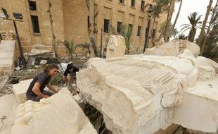 Bartosz Markowski, de l'université de Varsovie, et Robert Zukowski (c), de l'Académie polonaise des Sciences, inspectent une statue à l'entrée du musée de Palmyre, en Syrie, le 9 avril 2016