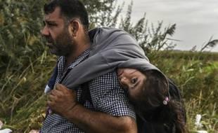 Un réfugié sa fille sur le dos le 14 septembre 2015 à Horgos en Serbie àla frontière avec la Hongrie