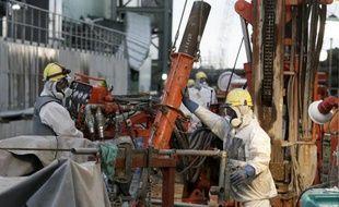"""Des ouvriers préparent des tuyaux pour la construction d'un """"mur de glace"""" censé réduire la quantité d'eau contaminée s'échappant dans l'océan, le 9 juillet 2014 à la centrale nucléaire de Fukushima, au Japon"""