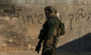 Un soldat israélien devant la maison palestinienne incendiée par des colons israéliens en Cisjordanie, le 31 juillet 2015