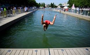Un homme plonge dans le bassin de la Villette.