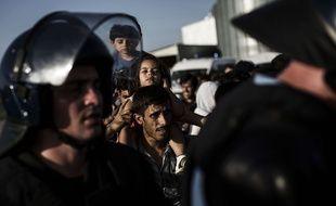 Un migrant porte une petite fille sur ses épaules, derrière des policiers anti-émeute déployés à la frontière serbo-croate, le 17 septembre 2015.