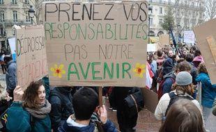 Des étudiants brandissent des pancartes appelant l'Etat français à renforcer son action climatique, le 1er mars à Paris.