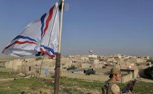 Novembre 2014, aux abords d'un village chrétien situé à 30 km au nord de Moussoul, en Irak. Un soldat de Dwekh Nawsha devant le drapeau du parti Assyrien, lors d'une surveillance (photo d'archives).