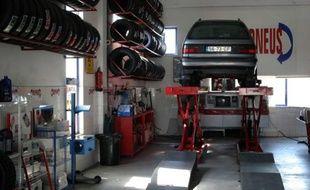 Changement de pneu sur une voiture chez un garagiste.