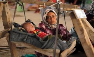 Une femme irakienne yazidi, qui a fui sa maison attaquée par des combattants de l'EI, regarde son bébé dans un immeuble en construction de la banlieue de Dohouk où ils ont trouvé refuge, le 16 août 2014