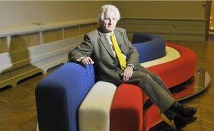 Pierre Paulin en 2008, assis sur sur un canapé créé par lui-même en 1969.