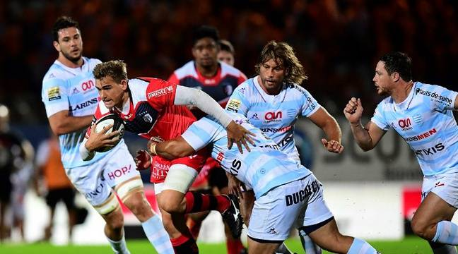 Le Toulousain Toby Flood tente d'échapper à la défense du Racing 92, le 4 septembre 2016 à Colombes. – F. Fife / AFP